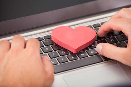 Cropped image of man dating online with heart shape on laptop 스톡 콘텐츠