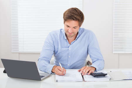 working desk: Portrait of confident mid adult businessman working at desk in office