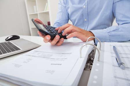 Bijgesneden afbeelding van zakenman berekenen van de belasting op het bureau in het kantoor Stockfoto