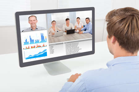 elearning: Rear view of businessman video conferencing on computer at desk in office