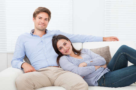 mid adult couple: Portrait of happy couple relaxing on sofa
