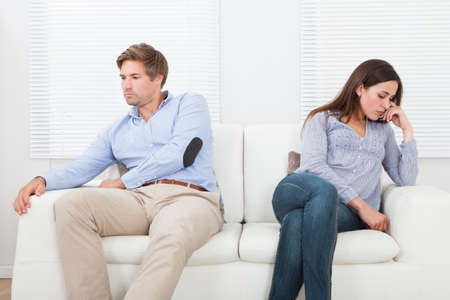 sad lady: Full length of couple ignoring each other while sitting on sofa at home