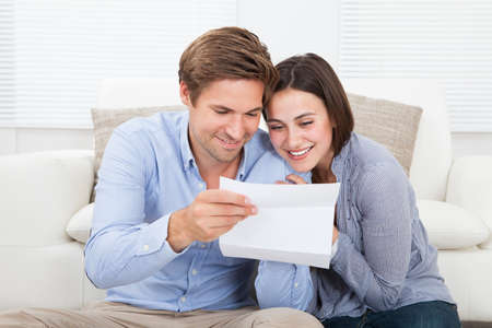 mid adult couple: Happy couple reading letter together at home