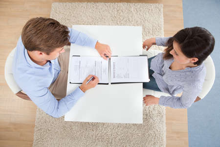 High angle view of businessman checking female candidates resume in office photo