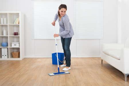 dweilen: Volledige lengte van de jonge vrouw reinigen hardhouten vloer van de woonkamer thuis
