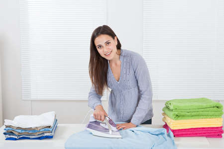 Portrait of woman ironing clothes in house photo