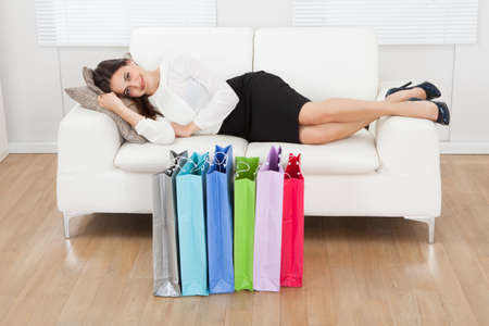 Full length portrait of smiling businesswoman lying on sofa with multicolored shopping bags on floor at home photo