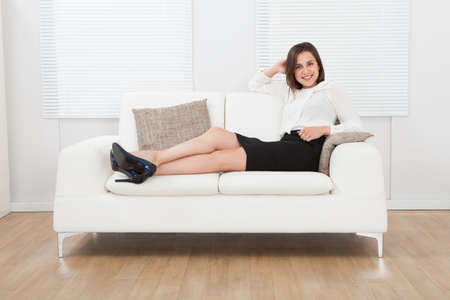 Full length portrait of young businesswoman sitting on sofa at home photo