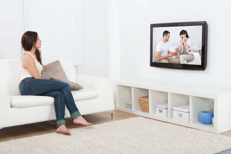 sofa television: Full length of young woman watching television while sitting on sofa at home Stock Photo