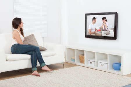mujer sentada: Integral de la mujer joven viendo la televisión mientras está sentado en el sofá en casa Foto de archivo