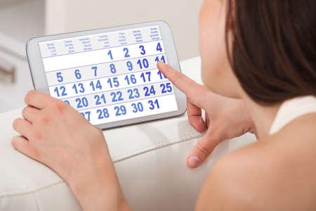 menstruacion: Recorta la imagen de una mujer joven con el calendario en la tableta digital en el hogar
