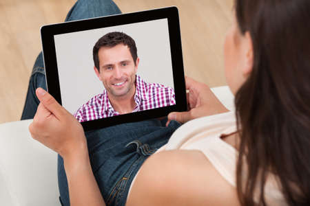 digital learning: High angle view of young woman video chatting with man at home