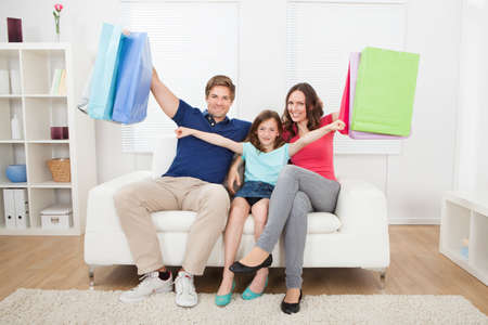 Portrait of happy family with shopping bags relaxing on sofa at home photo