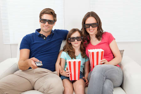 Smiling family in 3D glasses having popcorn while watching movie at home photo