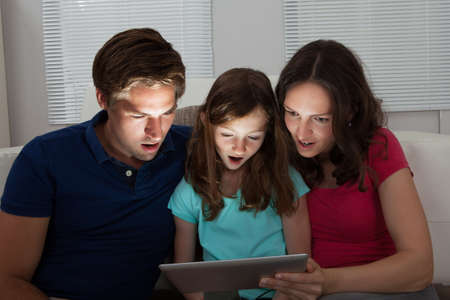 Shocked family of three using digital tablet on sofa at home Stock Photo