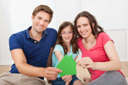 green man: Portrait of happy family holding green house model while sitting on floor at home