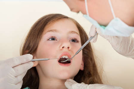 Close-up portrait of girl with mouth open going through dental examination in clinic