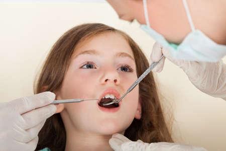 boca abierta: Close-up retrato de niña con la boca abierta de pasar por un examen dental en la clínica