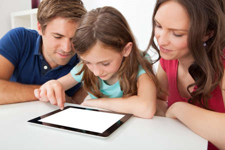 High angle view of parents with daughter using digital tablet with blank screen at house photo