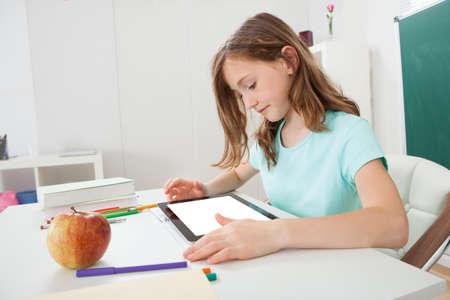 empty classroom: Cute schoolgirl using digital tablet at table in study room