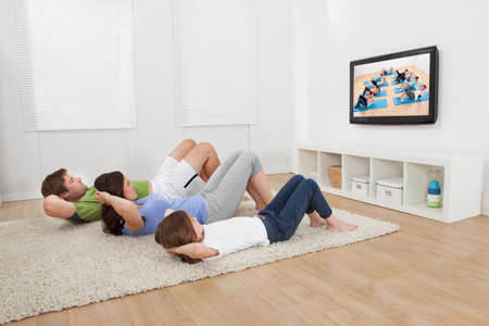 Full length of family doing situps while watching TV at home photo
