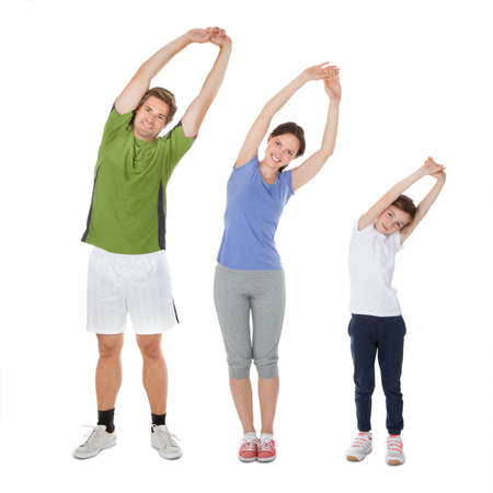 Full length portrait of fit family doing stretching exercise against white background photo