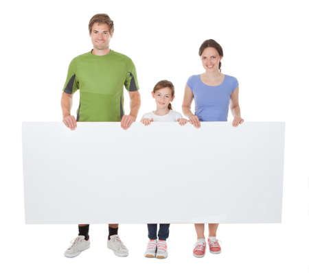 Full length portrait of family in sportswear holding blank billboard against white background photo