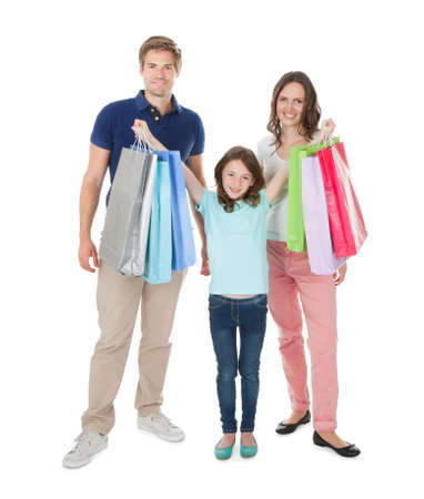 Full length portrait of happy family with shopping bags standing against white background photo