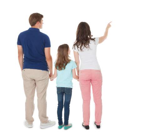흰색 배경 위에 가족에 게 뭔가 보여주는 여자의 전체 길이 후면보기