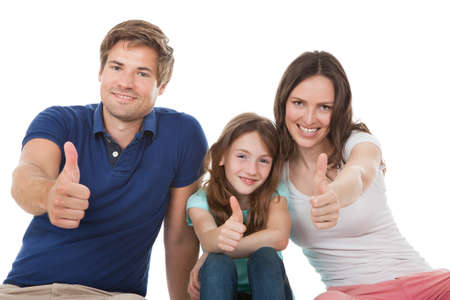 Portrait of happy family showing thumbs up together over white background