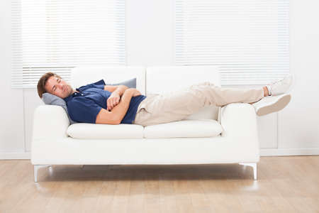 Full length of mid adult man sleeping on sofa at home photo