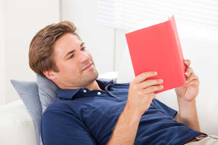 waistup: Mid adult man reading book while relaxing on sofa at home Stock Photo