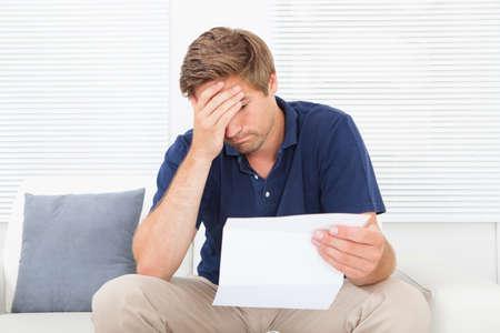 Benadrukt medio volwassen man met wetsvoorstel zittend op de bank thuis