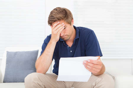 factura: Estresado hombre de mediana edad sosteniendo el billete mientras est� sentado en el sof� en casa