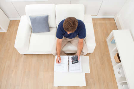 floor plans: High angle view of mid adult man calculating home finances in living room Stock Photo