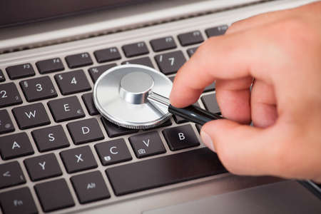 software portability: Closeup of mans hand examining laptop with stethoscope