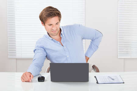 Tired businessman suffering from backache while working on laptop desk in office photo