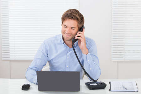 Smiling businessman looking away while communicating on landline phone in office photo