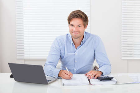 Portrait of confident mid adult businessman working at desk in office photo