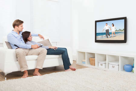 personas viendo television: Longitud total de pareja relajada en el sofá viendo la televisión en casa Foto de archivo