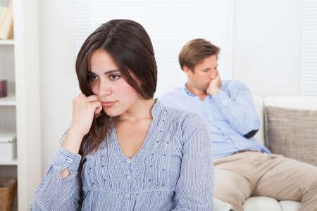 pareja enojada: Mujer joven trastornada con el hombre sentado en el sofá en el fondo como en casa