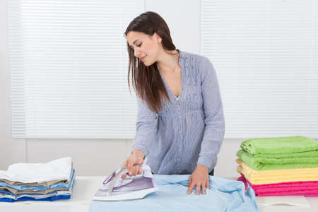 causal clothing: Portrait  of woman ironing clothes in house Stock Photo