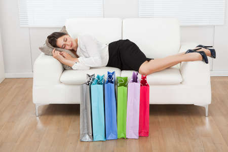 Full length of young businesswoman sleeping on sofa with shopping bags on floor at home photo