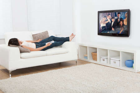 wish desire: Full length of young woman watching television while lying on sofa at home