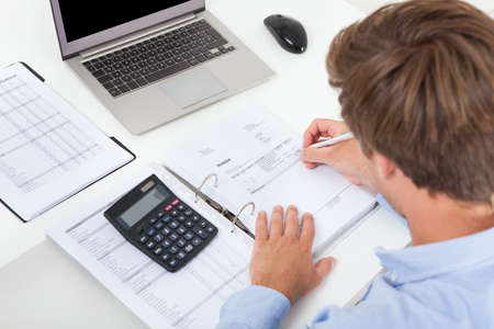 tax bills: High angle portrait of businessman calculating tax at desk in office