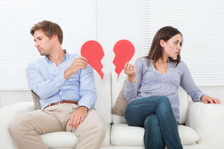 broken house: Full length of couple ignoring each other while sitting on sofa at home