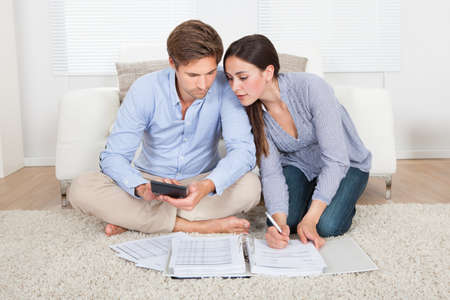 retirement homes: Full length of couple calculating budget in living room at home Stock Photo