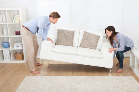 Full length of happy couple placing sofa in living room of new home Stockfoto