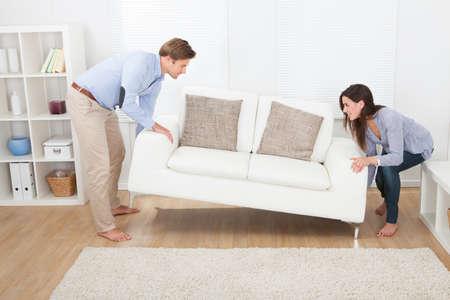 Volledige lengte van gelukkige paar plaatsen sofa in de woonkamer van de nieuwe woning Stockfoto