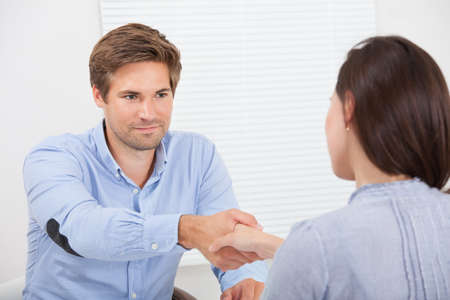 candidate: Smiling female candidate shaking hands with businessman in office